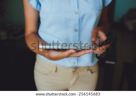 Businesswoman uses digital tablet. The tablet has a gray case and a glass screen. The woman in blue shirt. - stock photo