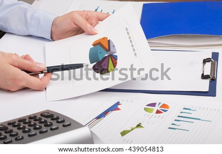 Businesswoman using calculator while analyzing graphs - stock photo