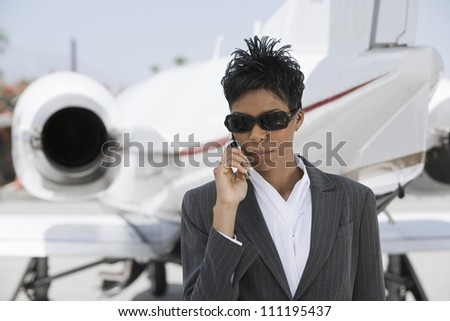 Businesswoman using cellphone with airplane in background - stock photo