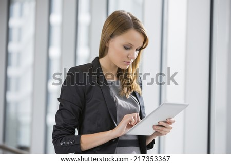 Businesswoman using digital tablet in office - stock photo