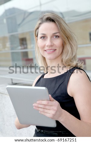 Businesswoman using electronic tab outdoors - stock photo