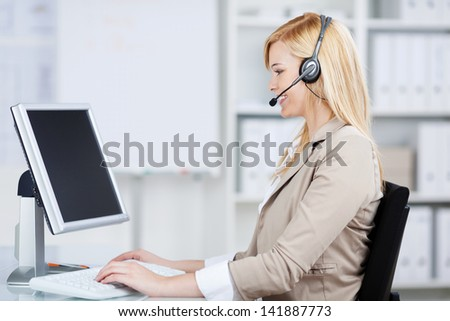 businesswoman using headset working on computer at business desk - stock photo