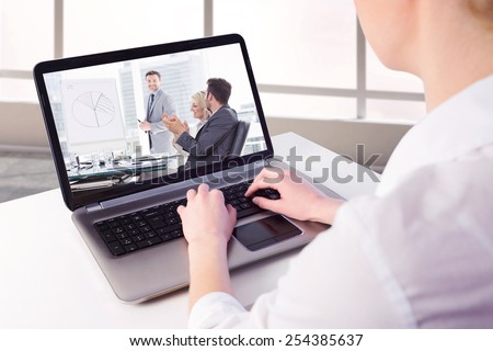 Businesswoman using her laptop against business people in office at presentation - stock photo