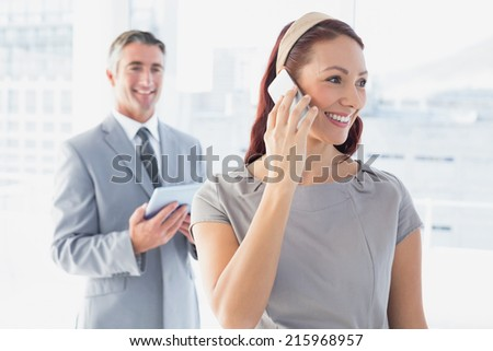 Businesswoman using her mobile phone in the office - stock photo