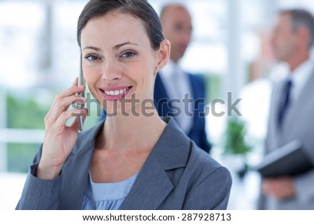 businesswoman using her phone with two colleague behind her at the office - stock photo