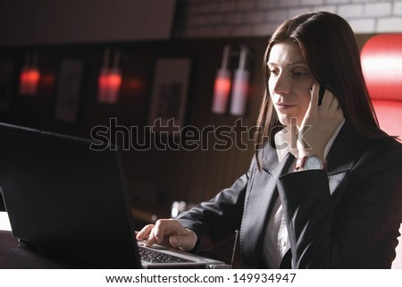 Businesswoman using laptop and mobile phone in the cafe - stock photo