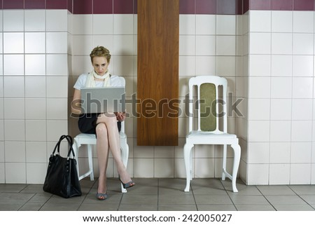 Businesswoman Using Laptop in Waiting Room - stock photo