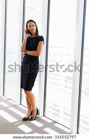 Businesswoman Using Mobile Phone In Office - stock photo
