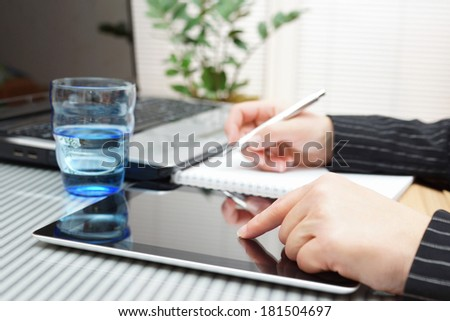 businesswoman using tablet, laptop and writing memo at office - stock photo