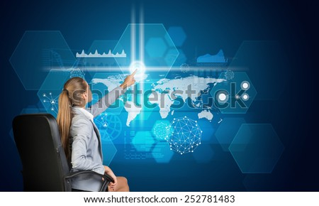 Businesswoman using virtual interface with world map, graphs and other elements, on blue background - stock photo