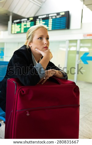 businesswoman waiting for her departure at the airport. symbolic photo for delays, flight cancellations and strikes. - stock photo
