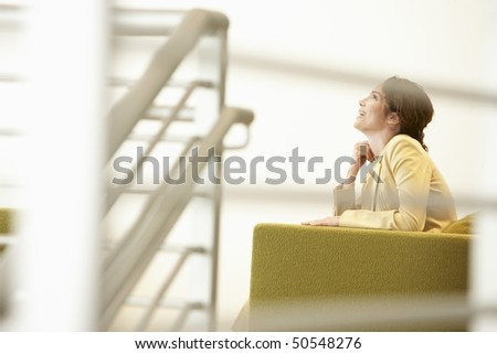 Businesswoman waiting on sofa in office - stock photo