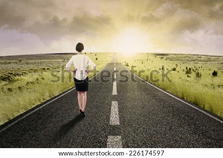 Businesswoman walk on the road to start her journey and gain bright future - stock photo