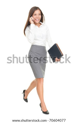 Businesswoman walking talking on mobile phone. Young stylish business woman smiling isolated on white in full body. Mixed-race chinese asian / white caucasian brunette female model. - stock photo