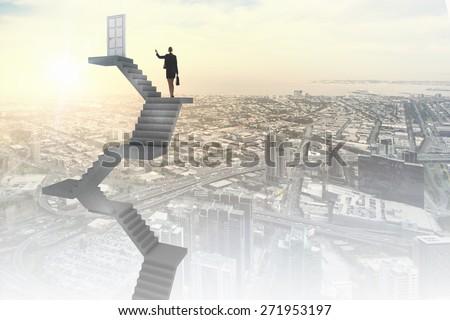 Businesswoman walking up staircase to door in sky - stock photo