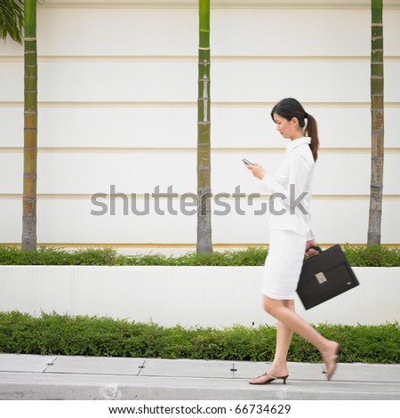 Businesswoman walking with cell phone and briefcase - stock photo