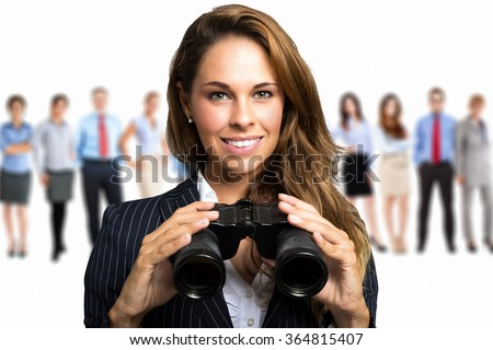 Businesswoman watching through binoculars in search of new opportunities - stock photo