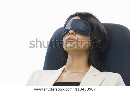 Businesswoman wearing eye mask and sleeping - stock photo