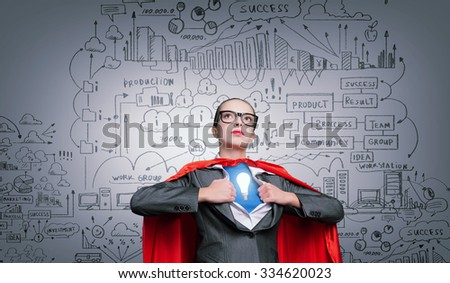 Businesswoman wearing red cape and opening her shirt like superhero - stock photo