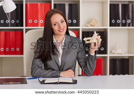 Businesswoman with a  model of plane sits on a workplace in the office. Travel agency. - stock photo