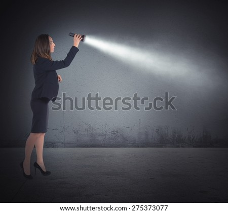 Businesswoman with a torch lights to search - stock photo