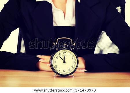 Businesswoman with alarm clock behind the desk - stock photo