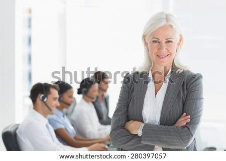 Businesswoman with arms crossed and executives using computers in office - stock photo