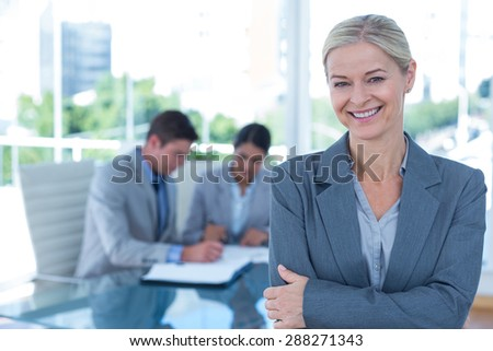 Businesswoman with arms crossed at office - stock photo