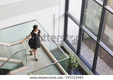 Businesswoman with briefcase pausing on stairway landing to look out - stock photo