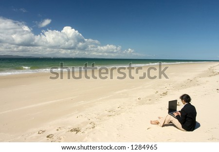 Businesswoman with business suit working at the beach - stock photo