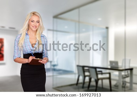 Businesswoman with checklist in office; teeth smile - stock photo