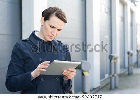 Businesswoman with digital tablet on front of warehouse - stock photo