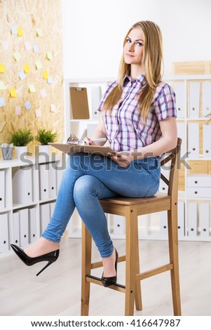 Businesswoman with document in hands sitting on wooden stool in office - stock photo