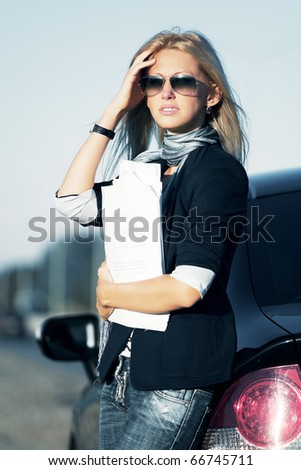 Businesswoman with financial reports against a highway. - stock photo