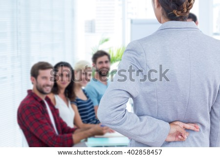 Businesswoman with fingers crossed behind her back over white background against businessman giving a presentation - stock photo
