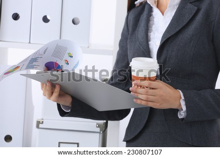 Businesswoman with folders and cup of coffee - stock photo