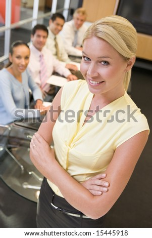 Businesswoman with four businesspeople at boardroom table in background - stock photo