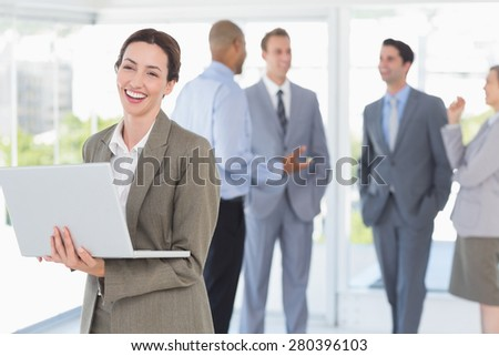 Businesswoman with his laptop and her colleagues behind in the office - stock photo