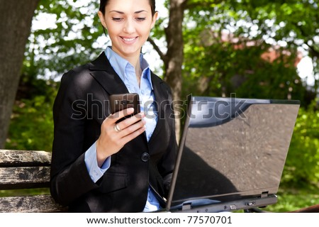 businesswoman with laptop and mobile phone in nature - stock photo