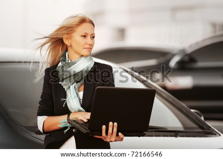 Businesswoman with laptop on the parking - stock photo