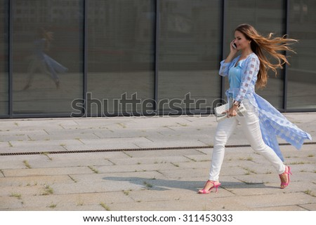 Businesswoman with long brown hair speaking over smart phone and hurrying up. Lady with blue coat on walking along the office building. - stock photo