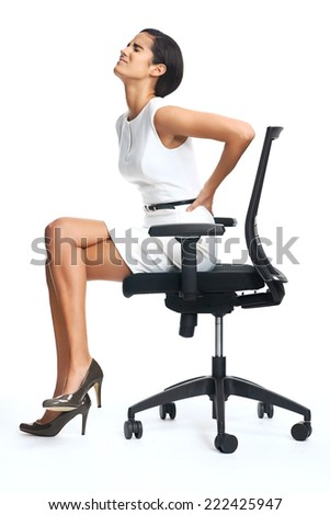 Businesswoman with lower back pain from sitting on office chair - stock photo