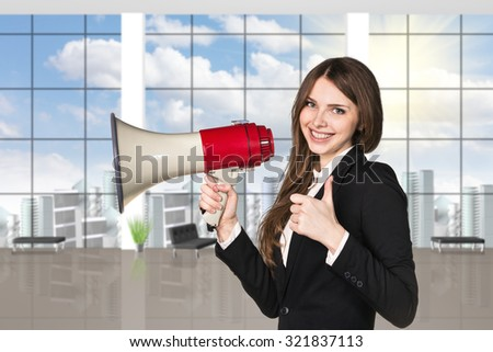 businesswoman with megaphone and thumbs up on the office background. - stock photo