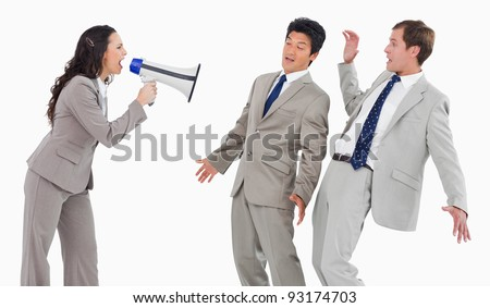 Businesswoman with megaphone shouting at colleagues against a white background - stock photo
