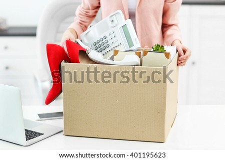 Businesswoman with moving box in office - stock photo