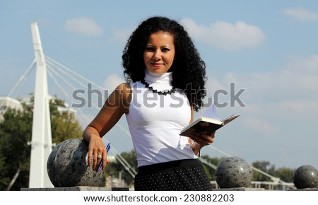 Businesswoman with notebook and pen at the street on sky background - stock photo