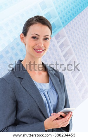 Businesswoman with phone against skyscraper - stock photo