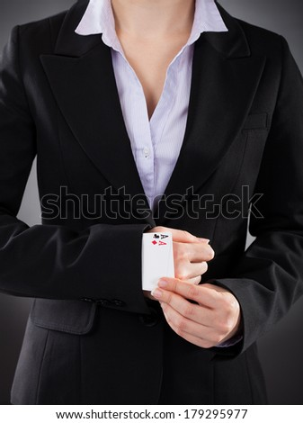 Businesswoman With Playing Cards Hidden Under Sleeve - stock photo