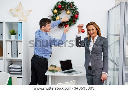 Businesswoman with red bubble looking at camera while her colleague decorating office Christmas wreath - stock photo