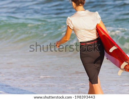 Businesswoman with surf near the ocean left office for surfing - stock photo